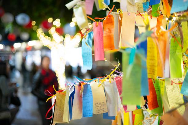 カリフォルニア州ロサンゼルスのリトルトーキョー地区にある「タンザク」に書かれた願い事は、小さな紙に書かれ、日本の願いの木に掛けられ、夜の屋外モールで撮影されました。 - 七夕の写真 ストックフォトと画像