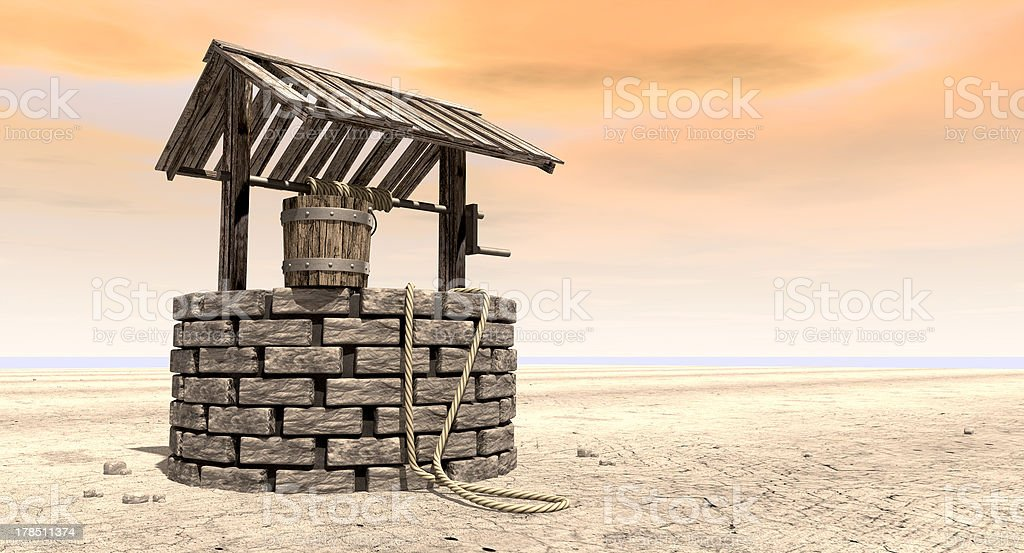 Wishing Well With Wooden Bucket On A Barren Landscape royalty-free stock photo