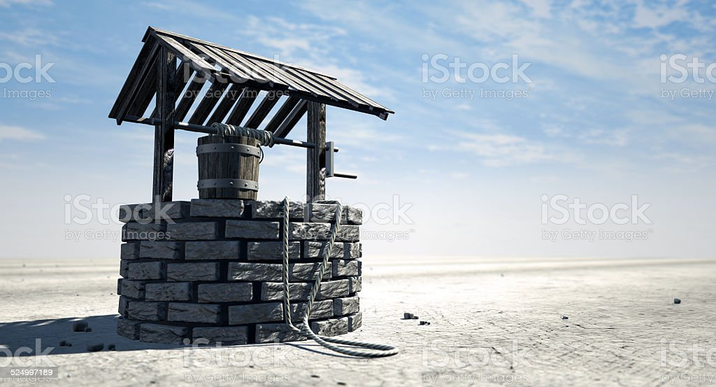 Wishing Well With Wooden Bucket On A Barren Landscape stock photo