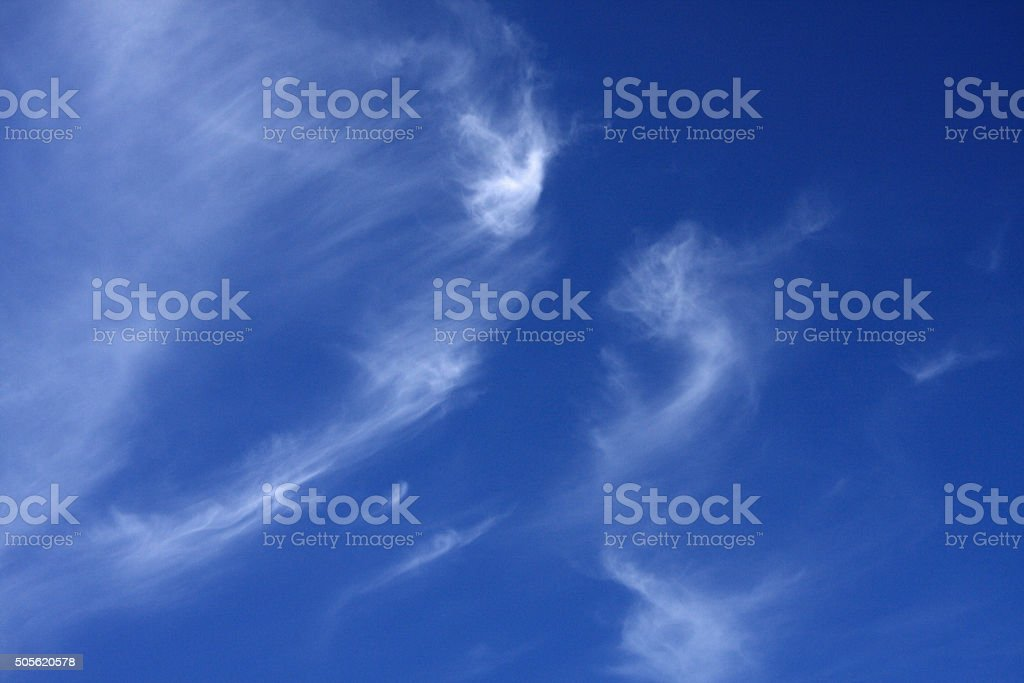 Wispy clouds in a bright deep blue sky stock photo