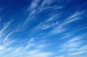 Full frame horizontal composition photography of blue sky during summer season with some wind, creates texture with some white clouds. Background picture, shot without people, in nature outdoor.