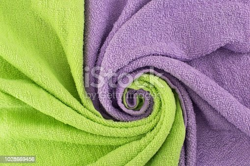 istock wisted in a spiral  textiles. Background with a wave of light green and purple towels. Background for design. 1028669456