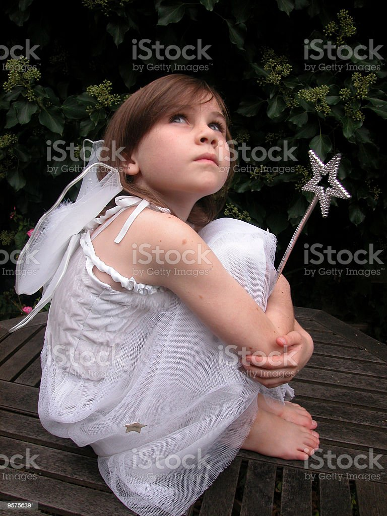 Wistful child in a white dress wings royalty-free stock photo
