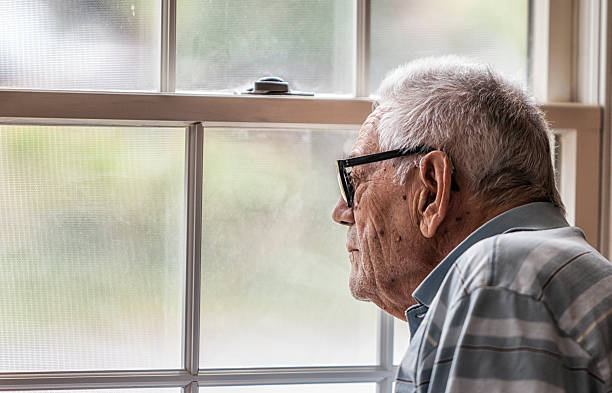 wistful senior man staring through hazy window - sole foto e immagini stock