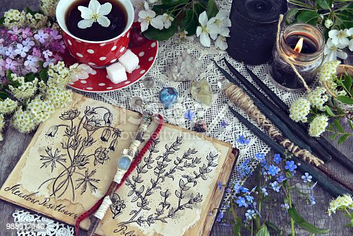 811119304 istock photo Witch book with magic and healing herbs, black candles and cup of tea 988017140
