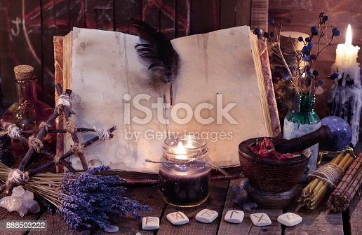 811119304 istock photo Witch book with pentagram, runes, magic objects and black candle 888503222
