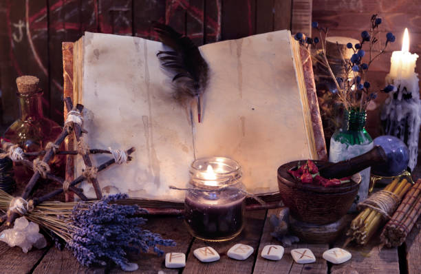 Witch book with pentagram, runes, magic objects and black candle stock photo