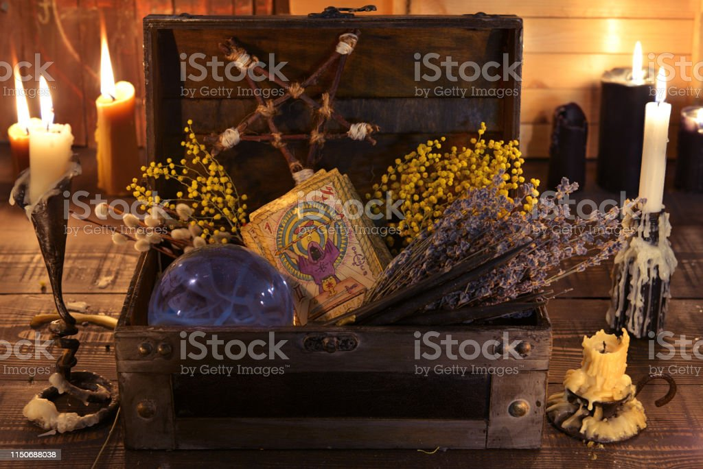Witch box with healing herbs, crystal ball, tarot cards and burning candles. Witch box with healing herbs, crystal ball, tarot cards and burning candles. Wicca, esoteric, divination and occult background with vintage magic objects for mystic rituals Alchemy Stock Photo