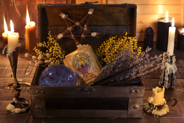 Witch box with healing herbs, crystal ball, tarot cards and burning candles. stock photo