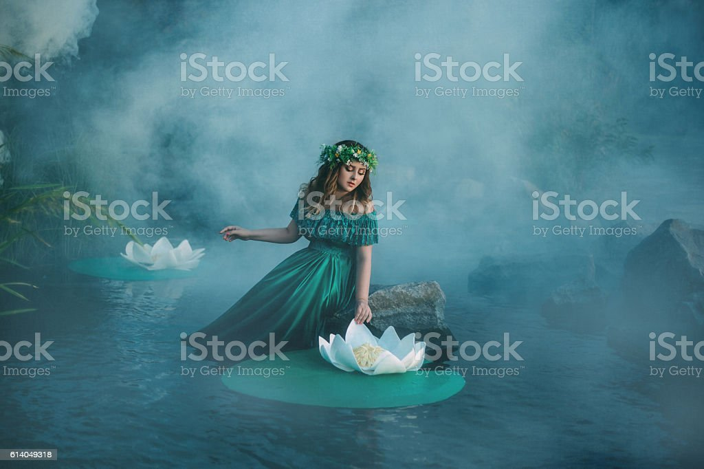 Witch casts a spell on the water in the fog stock photo