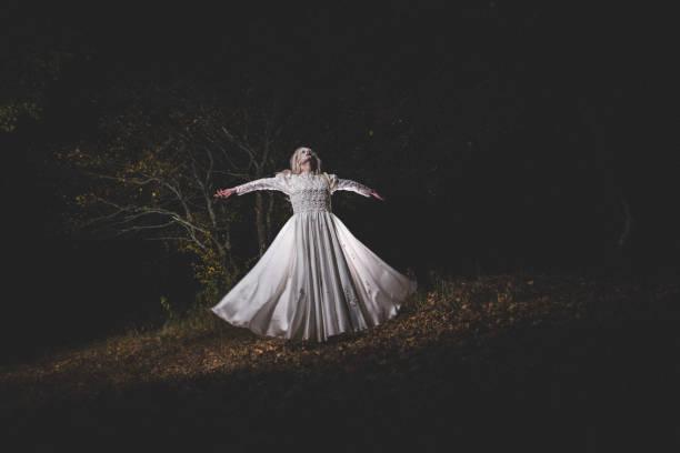 hexe im weißen kleid im dunklen wald - coole halloween kostüme stock-fotos und bilder