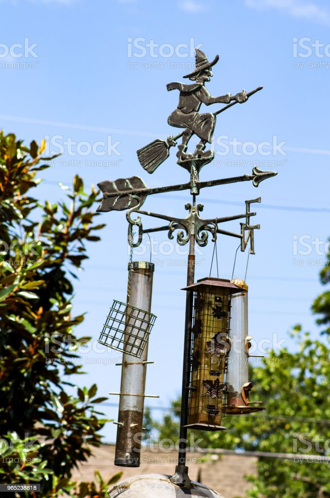 Witch on broom weather vane with bird feeders hanging from it zbiór zdjęć royalty-free