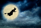 Witch Riding On Broom In Front Of Hazy Full Moon