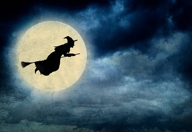 Witch Riding On Broom In Front Of Hazy Full Moon stock photo