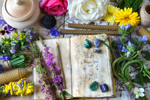Witch spell book, calendula, rose flowers, reiki crystals and candles on wooden table. stock photo