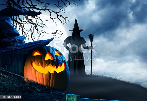 A witch on a small hill stands with her broomstick as she is silhouetted against a rising full moon on Halloween night.  An illuminated jack o'lantern and a witch's hat and broomstick sit in the foreground.