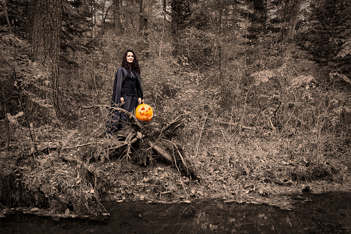 Witch with pumpkin by the river