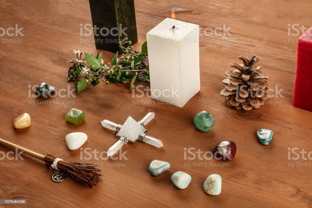 Wicca Christmas.Witchcraft A Photo Of A Wicca Altar With Candles Crystal Stones And Norse Runes With A Little Broom With A Pentacle On A Dark Rustic Wooden Background