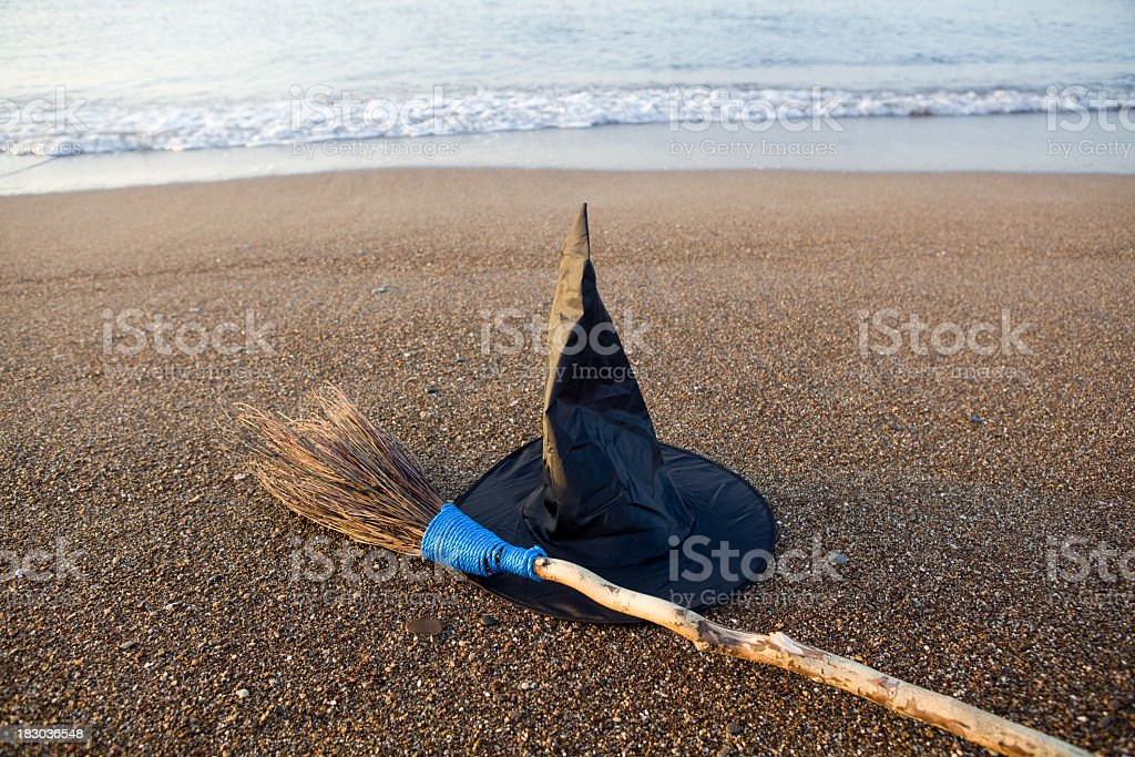 Witch's Hat And Broom On Beach Sand By Sea Vawes stock photo