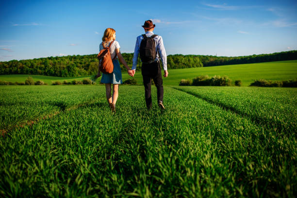 With a backpack, a man in a hat and a woman with long hair go along the path. A couple walks along the meadow stock photo