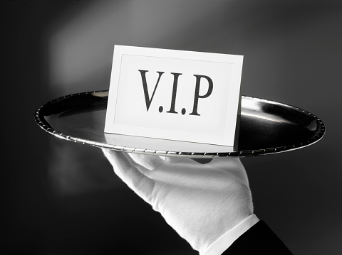 First class service. Waiter holding a Very important person VIP card on a silver tray. Click on the link below to see more of my business images.