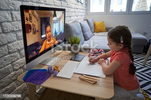 Charming 5 year's old girl having a video call with her sister via computer app and they both painting, drawing during home isolation