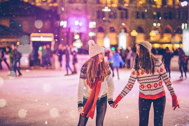 With bestie for Christmas Friends having so much fun while ice skating at night. Wearing warm clothing. City is decorated with christmas lights. ice skating stock pictures, royalty-free photos & images