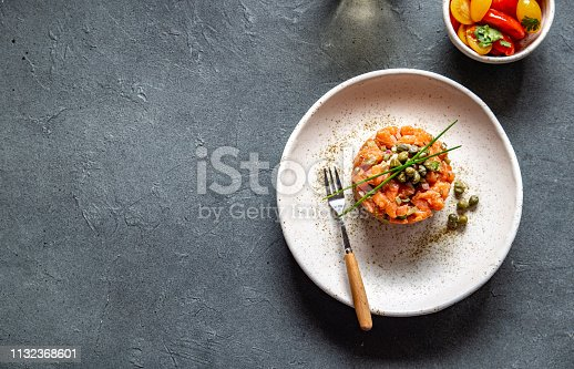 istock SALMON TARTAR with capers and purple onion on white plate, gray background 1132368601