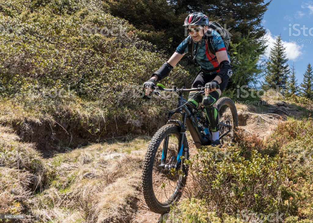 With electric mountainbike on bumpy single trail in the Carinthian mountains, Austria. stock photo