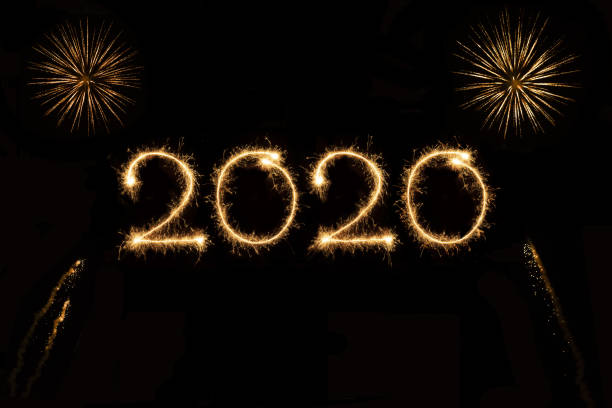 2020 with fireworks 2020 written with sparklers and fireworks jude beck stock pictures, royalty-free photos & images