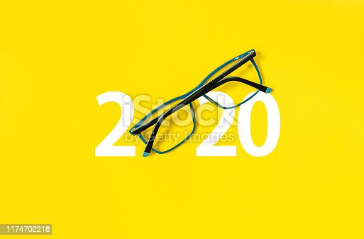 istock 2020 with glasses on yellow isolated background 1174702218
