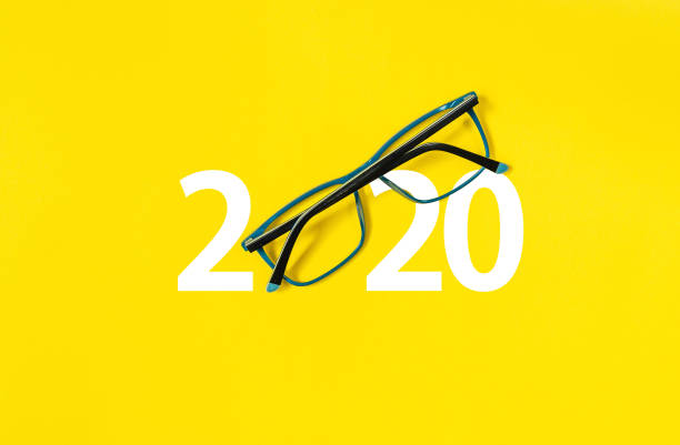 2020 with glasses on yellow isolated background stock photo