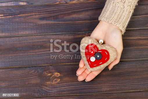 istock with heart in hands on wooden background. Valentine's Day concept with copyspace 891501900