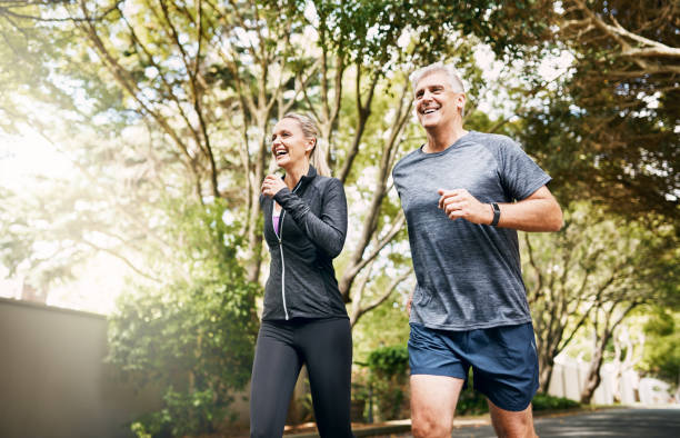 With her by my side I can run miles Shot of a mature couple out jogging on a sunny day mature couple stock pictures, royalty-free photos & images