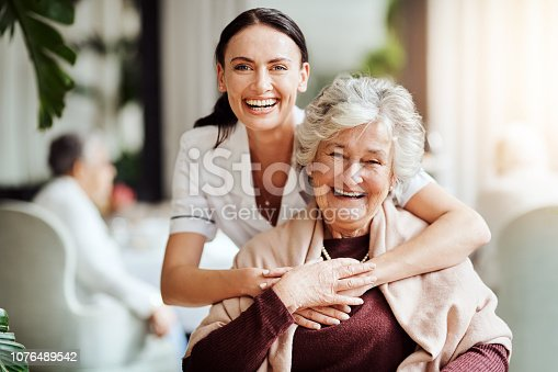 Portrait of a young nurse embracing an elderly woman in a retirement home