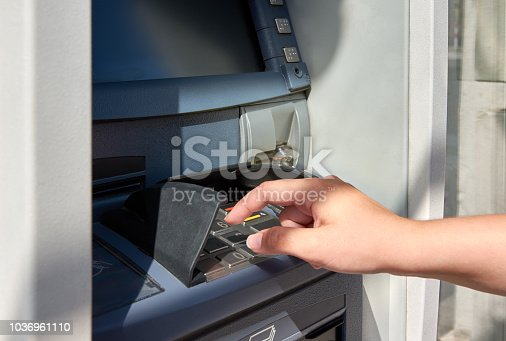 istock ATM with keyboard and hand of young woman tapping pin code 1036961110