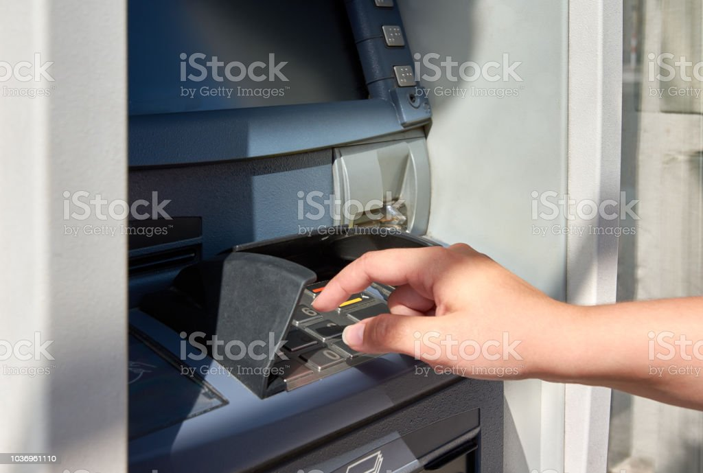 ATM with keyboard and hand of young woman tapping pin code stock photo