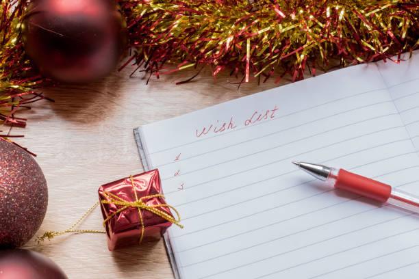 mit liste auf neujahr 2018. notebook und schwarze pfanne auf tisch rund um silber garland und paar weihnachten spielzeug. - weihnachts wunschliste stock-fotos und bilder
