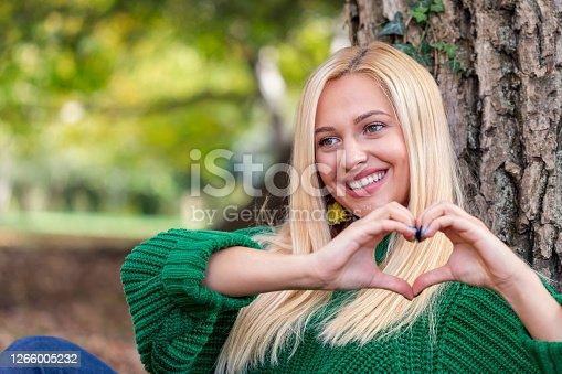 Young beautiful woman making heart shape