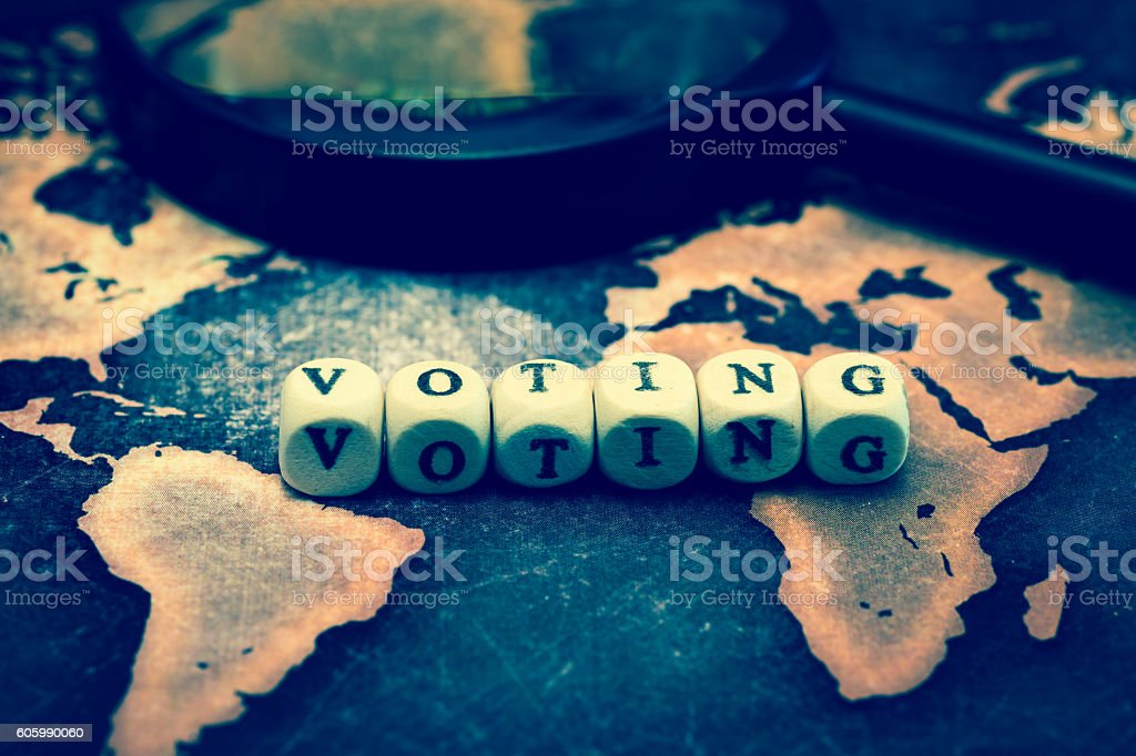 VOTING with magnifying glass on grange world map stock photo