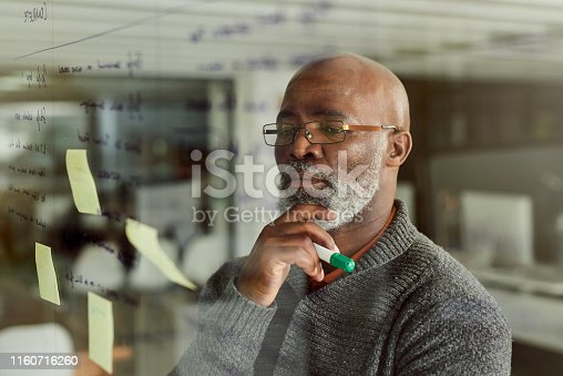 Cropped shot of a mature businessman brainstorming with notes on a glass wall