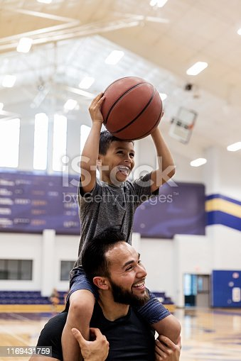 The mid adult uncle puts his young nephew on his shoulders and both have fun shooting baskets at the gym.