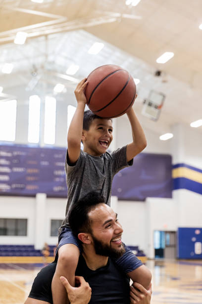 With nephew on uncle's shoulders, both have fun shooting baskets stock photo