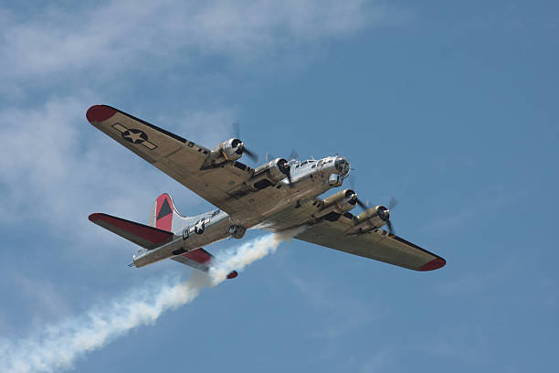 B-17G with one engine smoking B-17G with one engine smoking bomber plane stock pictures, royalty-free photos & images