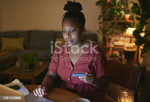 Shot of a young woman using a laptop and credit card at home at night