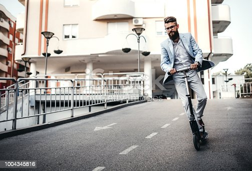 Hipster men riding on push scooter while traveling to the work