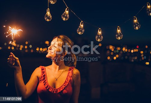Young, smiling, pretty woman with sparkler on the rooftop.