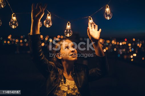 Young, beautiful, woman with string light on the rooftop.