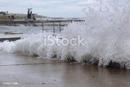 With the strong wind came huge waves that crash against the walls of the shore and shatter in all directions. Foamy sea. The power of the sea. The power of mother nature. Rainy weather. Paphos, Cyprus.
