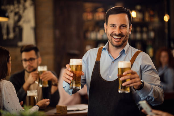 With us is always happy hour! Happy waiter holding two glasses of beer and looking at camera while working in a pub. lager stock pictures, royalty-free photos & images